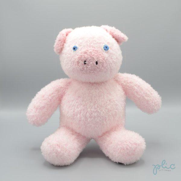 Peluche de 30cm de haut représentant un petit cochon, tricotée par Plic.