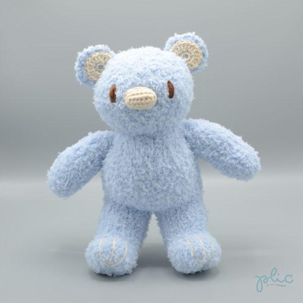 Peluche de 30cm de haut représentant un ourson bleu pâle, tricotée par Plic.