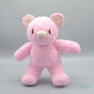Peluche de 30cm de haut représentant un ourson rose pâle, tricotée par Plic.