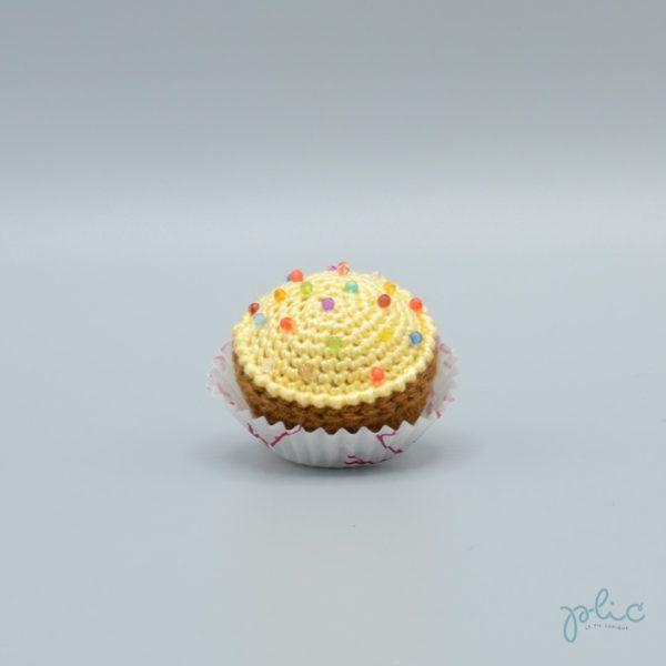 petit gâteau de 4 cm de haut, recouvert d'un disque jaune pâle crocheté par Plic et décoré de perles colorées.