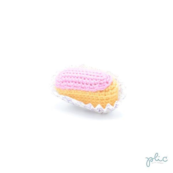 mini éclair au crochet de 6cm de long, recouvert d'une bande rose crochetée, le tout réalisé par Plic.
