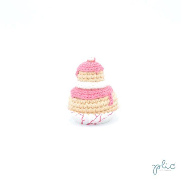 Petit gâteau de 6,5cm de haut, composé de 2 choux crochetés superposés, recouverts de disques rose moyen crochetés, d'un tour blanc au tricotin et d'une perle nacrée, le tout réalisé par Plic.