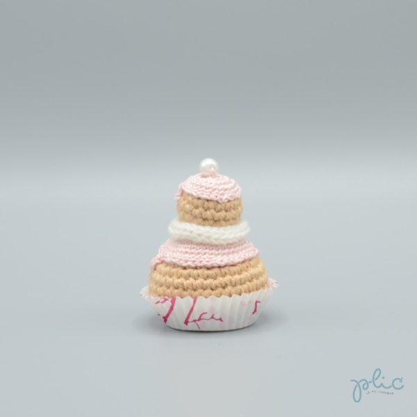 petit gâteau de 6,5cm de haut, composé de 2 choux crochetés superposés, recouverts de disques rose pâle crochetés, d'un tour blanc au tricotin et d'une perle nacrée, le tout réalisé par Plic.