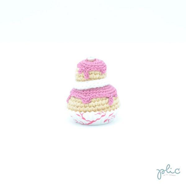 petit gâteau de 6,5cm composé de 2 choux de grandeur différente réalisés au crochet, recouverts de disques rose foncés crochetés, d'un tour blanc au tricotin et d'une perle nacrée, le tout réalisé par Plic.