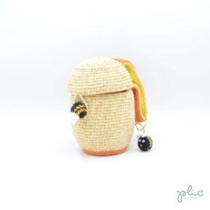Sac aumônière de 16cm de haut et12cm de diamètre, muni d'une anse de 13cm et représentant une ruche décorée de 2 abeilles, le tout crocheté par Plic.