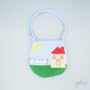 Sac rond de 17cm de haut, muni de 2 anses de 35cm, représentant une maison et la lessive sèchant sur un fil dans le jardin, le tout tricoté par Plic.